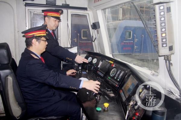 喻伟站在旁边指导年轻的司机掌握火车驾驶。
