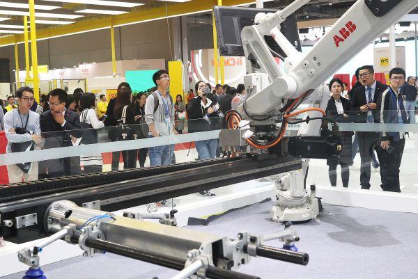 资料图片:11月7日,第十九届中国国际工业博览会在上海正式对公众开放。这是参观者在观摩ABB集团的工业机器人展区。新华社记者 陈飞 摄