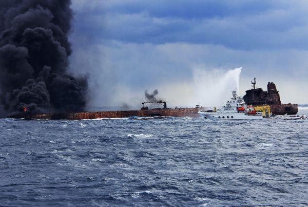 """1月12日,上海海事局的救援船只在向""""桑吉""""轮喷射泡沫降温灭火。"""