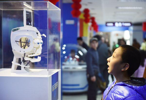 """资料图片:2月18日,在福建省科技馆,小朋友与能模仿人表情的""""表情机器人""""互动。新华社记者 宋为伟 摄"""