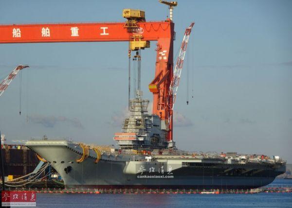 资料图片:夕阳下的001A国产航母,背景是巨大的大连船舶重工龙门吊。