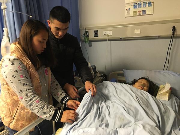 佘军(中)和亲属在医院照顾摔伤的唐坤香。