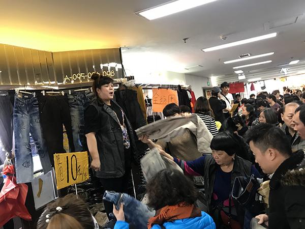 商户们站在高处吆喝甩卖。澎湃新闻记者 赵实 图