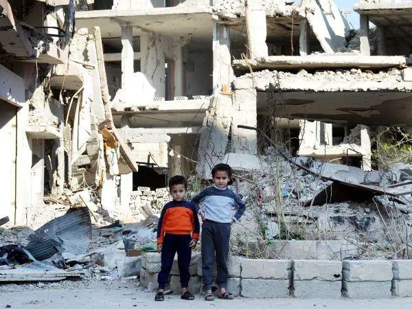 △资料图/2017年10月28日,在叙利亚中部城市盖尔亚廷,两名儿童站在被战火摧毁的居民楼前。