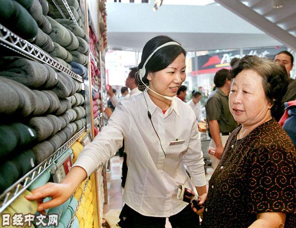 资料图片:上海优衣库的店员在为顾客讲解。(图片来源:《日本经济新闻》网站)