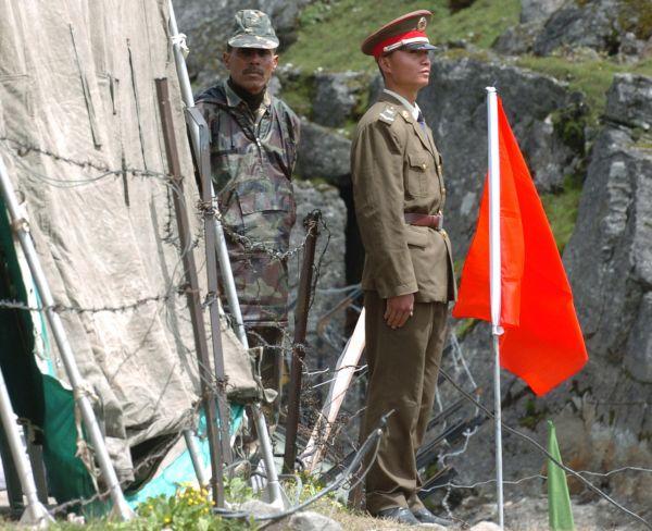 资料图片:2006年7月5日,在中印边境乃堆拉山口,一名中国边防军人(右)与一名印度边防军人隔着边界的铁丝网值勤。新华社记者韩传号摄