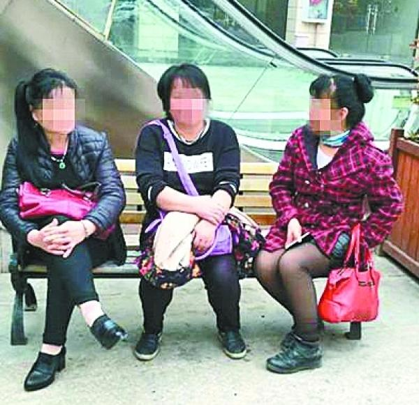 中间为假媒婆张某,右边为逃跑的假媒婆彭某。 武汉晨报 图