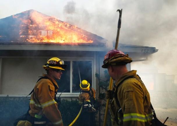 图为消防员继续扑救大火。
