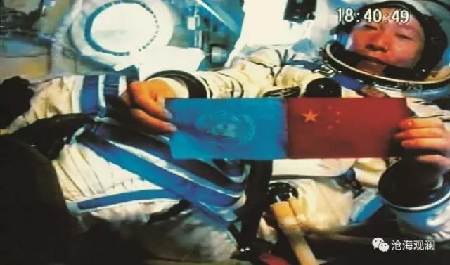 杨利伟在太空展示中国国旗和联合国旗。