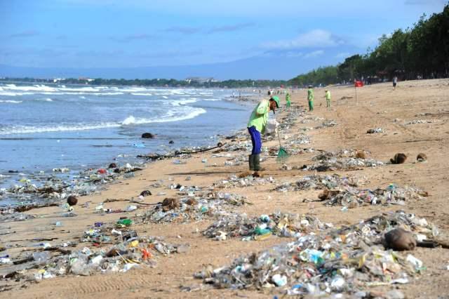 2017年12月19日,印度尼西亚巴厘岛一处海滩,工人在清理垃圾。(新华/法新) 新华社北京12月29日电(记者杨舒怡)印度尼西亚巴厘岛是著名旅游胜地,沙细滩阔,海水湛蓝,每年吸引全球各地大量游客前往度假。然而,这座旅游岛正面临海洋垃圾成灾的严峻问题,当地官员上月不得不宣布进入垃圾紧急状态。 库塔、金巴兰等处的海滩,拥有巴厘岛景色最美的海滨浴场。然而,如今游客们却要在各种垃圾空隙之间寻找一块落脚处,才能勉强晒个日光浴;冲浪者们稍不小心,就有可能被海浪裹挟的垃圾砸个正着。 食品包装盒、吸管、塑料袋
