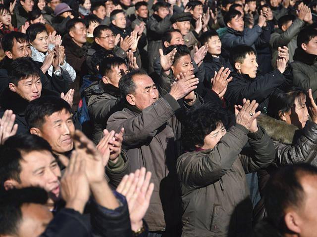 11月29日,平壤街头,民众驻足观看巨型显示屏播报的成功试射弹道导弹新闻。(新华/法新)