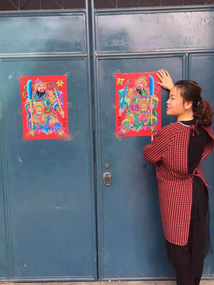 腊月二十八,妹妹在老家宅院贴春联、门画。受访者供图