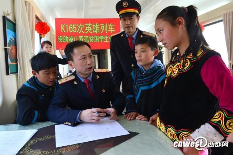 2010年,费耀斌被调往K165车队,跟随列车在宝成线跑了7年,图为费耀斌所在的K165车队与大凉山的彝族贫困生签订资助协议。(唐振江 摄)