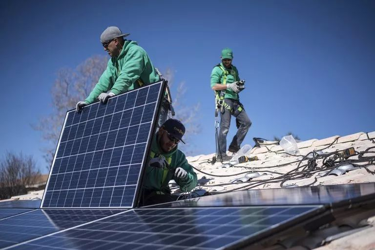 ▲美国工人在安装太阳能电池板。(彭博新闻社)