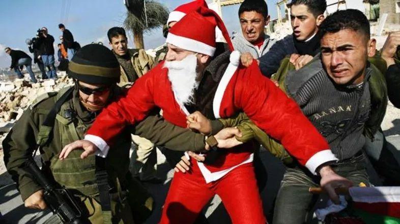 ▲12月23日,扮成圣诞白叟的巴勒斯坦抗议者与以色列士兵产生抵触。(巴勒斯坦消息网)