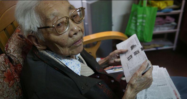 李老查阅报纸上关于南京大屠杀的报道