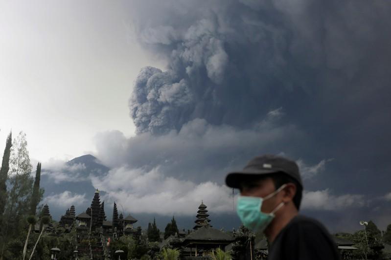 巴厘岛阿贡火山喷发大量火山灰到空中,当地民众戴口罩防吸入火山灰。