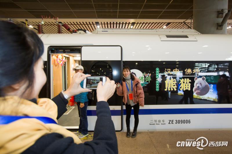 12月6日,西安北站,乘坐首趟西安北至成都东D4251次动车组的旅客在站台上合影。