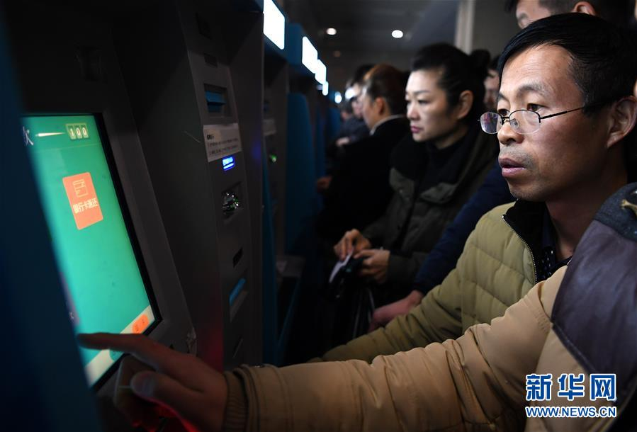 12月4日凌晨,在合肥一家医院的自助挂号机前,王传俊在为怀二宝的妻子挂妇产科的号。新华社记者 刘军喜 摄
