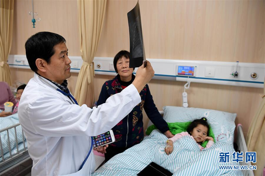 在安徽省立医院南区儿科病房,儿科副主任医师朱守法在给小患者诊治(12月6日摄)。新华社记者 刘军喜 摄