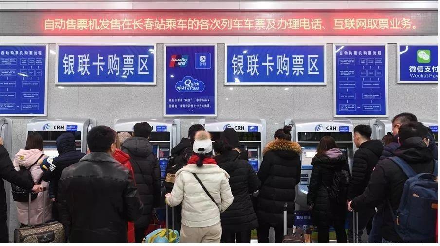 ▲1月3日,旅客在长春火车站售票大厅自动售票机前排队购票、取票。图片来自新华社