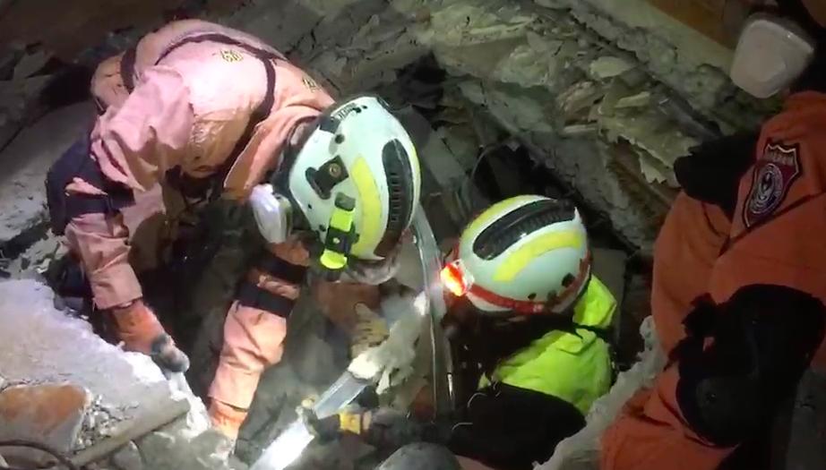 """救援人员正在倾斜的大楼里凿洞(图片来源:""""联合新闻网"""")"""
