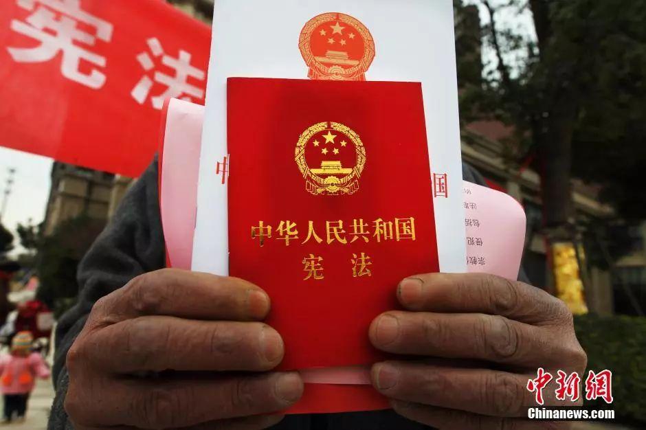 资料图:民众手捧《中华人民共和国宪法》单行本。(中新社发许丛军 摄 图片来源:CNSPHOTO)