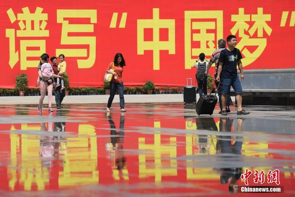 """资料图:2015年5月3日,湖南长沙南站,""""谱写'中国梦'""""巨大标语前的劳动者。中新社发 廖攀 摄"""