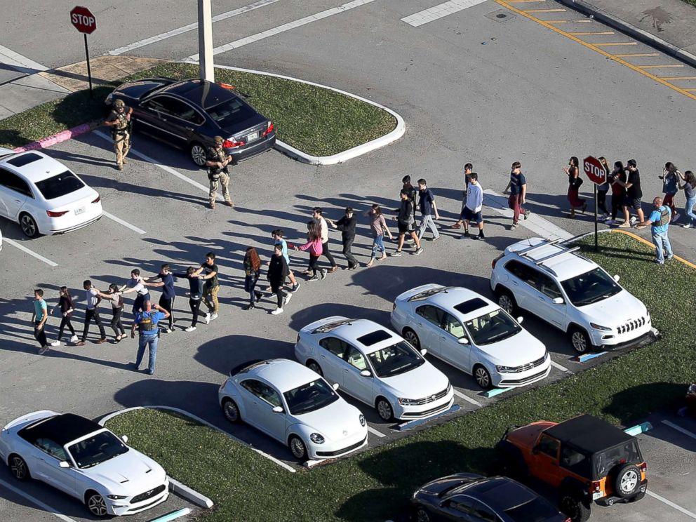 图为2月14日枪击案发生后,人们被带离学校。(图源:ABC新闻)