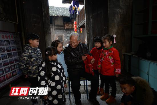 老人在跟孩子们讲述沅水的故事。卢七星 摄