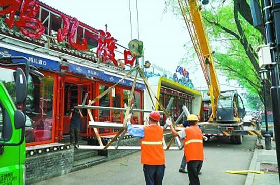 """工人在拆除""""鸦儿渡口""""酒吧二层违建。北京晚报 图"""
