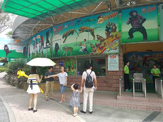 广州动物园工作人员在动物行为展示馆门前对有意愿观看马戏表演的游客进行劝阻。