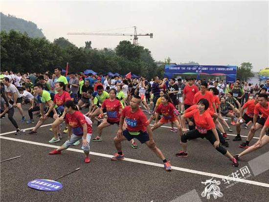 开赛前,参赛选手随着引领员做起了热身运动。 记者 姜力菘 摄