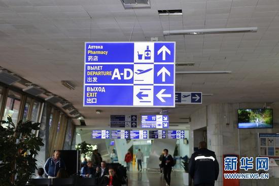 在白俄罗斯首都明斯克机场,乘客们从中文标识的指示牌下面走过。新华网记者魏忠杰摄