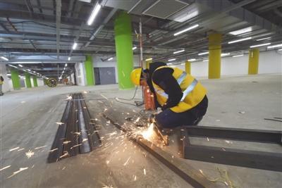 京雄城际新机场站上方是机场停车楼,图为昨日工人在现场施工。