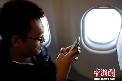 资料图:在东航MU5137航班上,旅客全程在飞行模式下可以使用手机。殷立勤 摄