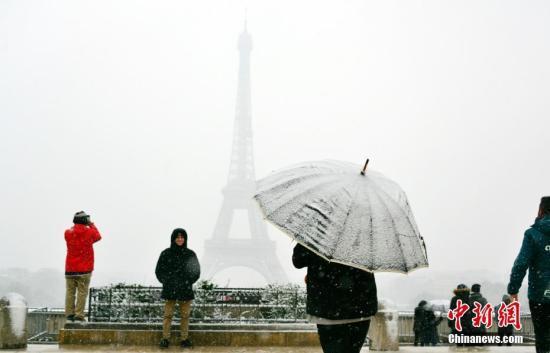 法国气象局维持对27个省份的冰雪橙色警报。受降雪影响,著名旅游景点埃菲尔铁塔6日全天关闭。图为游人6日在巴黎以埃菲尔铁塔为背景拍摄雪景。中新社记者 龙剑武 摄