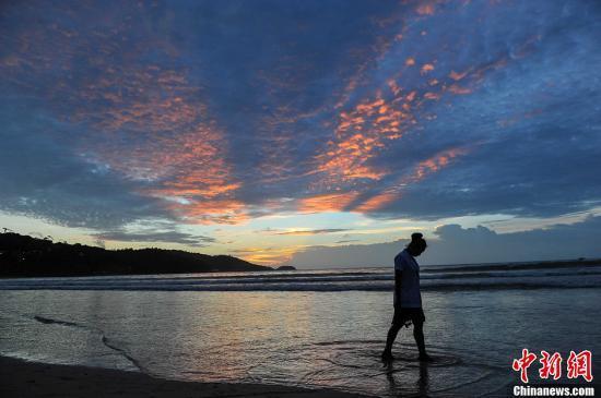 资料图为一名游客从泰国海滩上走过。洪坚鹏 摄