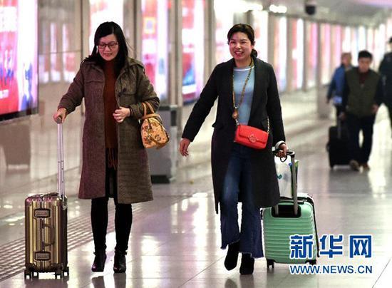 3月12日,两位旅客从郑州火车站出站。当日是2018年春运的最后一天,为期40天的2018年春运落下帷幕。 新华社发(李嘉南 摄)