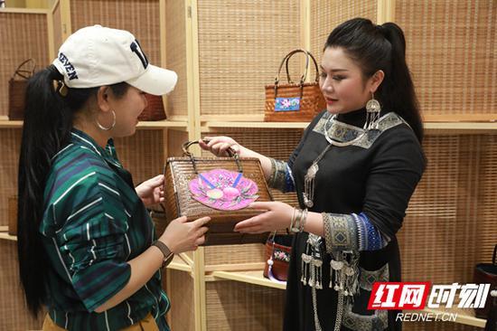 阿苗千千在给顾客介绍苗绣。