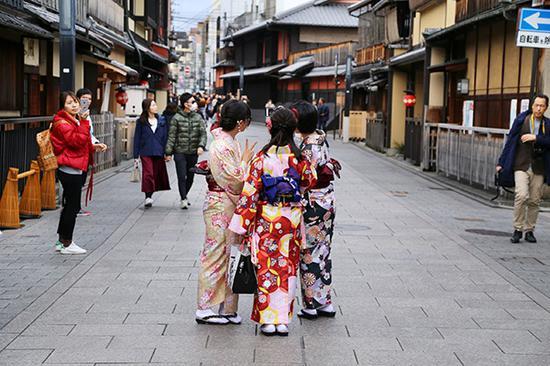 游客也喜欢穿着和服站在花见小路上拍照。东方IC 图