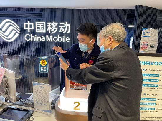 (营业厅服务人员为老人用户提供一对一手机指导)