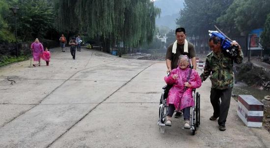 8名仙台山景区工作人员轮流帮助下依靠轮椅和担架帮助近90岁高龄的老人下山