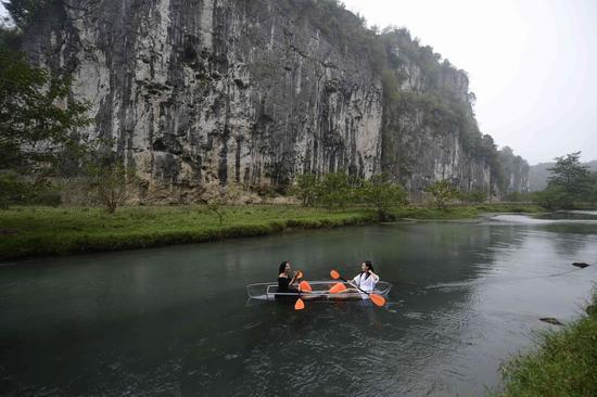10月24日,湖南湄江三道岩门全透明船开放,四位体验者乘坐着透明船在河中划行,漂浮在水面的游人置身于山水美景中,如在画中游。杨华峰摄