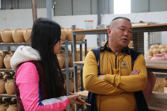 云南窑上陶艺文化发展有限公司赵明良(右)谈彩陶