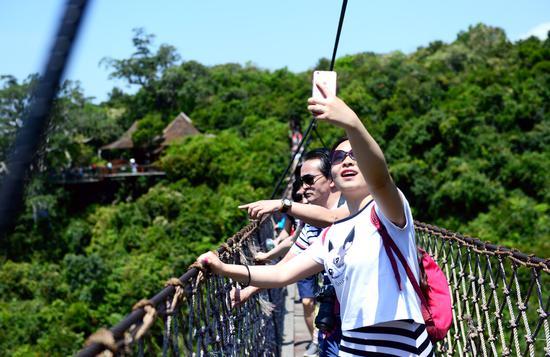 游客过江龙索桥赏春光