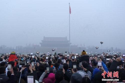 资料图为北京天安门广场上民众在雾中观看升旗仪式。 中新社记者 盛佳鹏 摄