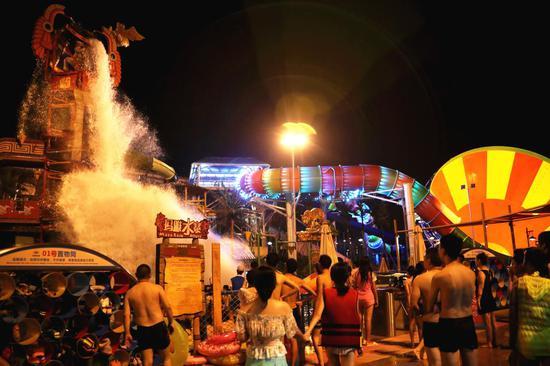 大量夜场游客在玛雅水寨下感受巨桶翻滚的清凉