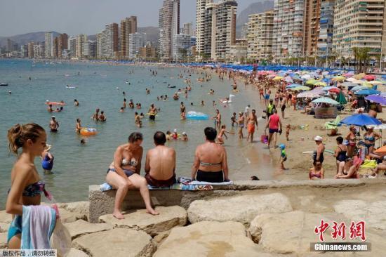 资料图:游客在西班牙贝尼多姆的海滩享受日光浴