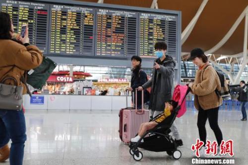 资料图:旅客带着孩子前往办票柜台办理登机手续。 殷立勤 摄